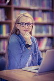 Student with smartwatch using laptop in library. At the university Royalty Free Stock Photo