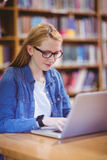 Student with smartwatch using laptop in library Stock Photography