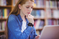 Student with smartwatch using laptop in library Royalty Free Stock Photo