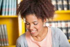 Student Smiling Against Bookshelf i arkiv fotografering för bildbyråer