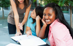 Student smiling at camera. Young lady smiling at camera while friends study in background Royalty Free Stock Images