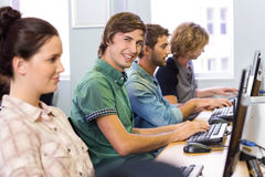 Student smiling at camera in computer class. Male student smiling at camera in computer class Royalty Free Stock Photography