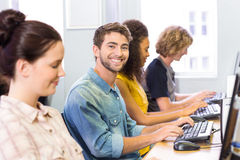 Student smiling at camera in computer class. Male student smiling at camera in computer class Stock Image