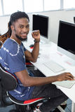 Student smiling at camera in computer class. Male student smiling at camera in computer class Stock Photo