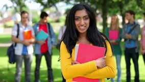 Student smiling at camera with friends standing behind her stock footage