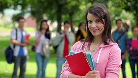 Student smiling at camera with friends standing behind her on grass stock footage