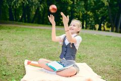 Student is smiling happily and is holding a red apple overhead. schoolgirl sitting on a blanket in a park with books royalty free stock photo