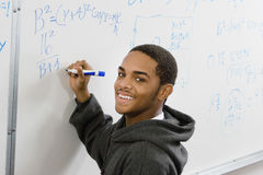 Student Solving Algebra Equation On Whiteboard. Portrait of smiling male student solving algebra equation on whiteboard in classroom stock photos