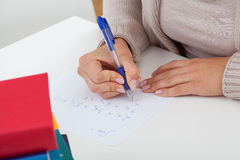 Student solving the math problems. Student writing the math problems on the piece of paper Stock Photography