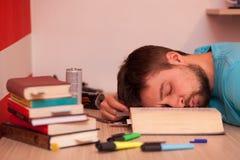 Student som är stupad sovande i mitt av en stor bok Arkivbild