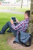 Student som använder hans minnestavlaPC utanför benägenhet på träd royaltyfri foto