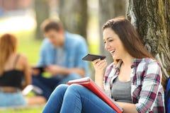 Student som använder stämmaerkännande med en telefon fotografering för bildbyråer