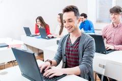 Student som arbetar på bärbar datorPC i högskola Arkivbilder