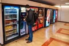 Student som betalar för drinkarna från varuautomaten royaltyfria bilder