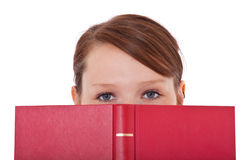 Student som döljer hennes framsida bak boken Arkivbilder