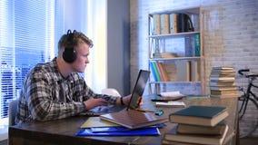 Student som direktanslutet lär med hörlurar och bärbara datorn stock video