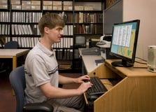 Student som för datorforskning i ett arkivarkiv Royaltyfri Foto