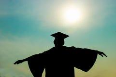 Student som fördjupa armarna när berömutbildningsavläggande av examen Arkivbild