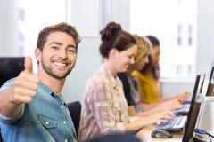 Student som gör en gest tummar upp i datorgrupp Arkivfoto