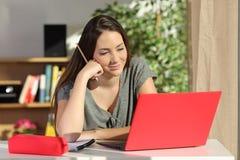 Student som hemma e-lär genom att använda en bärbar dator royaltyfri foto