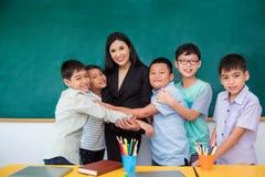 Student som kramar deras lärare i klassrum royaltyfria bilder