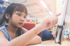 Student som lär hur man använder minnestavlan i klassrum arkivbild