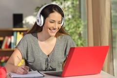 Student som lär på linje med en bärbar dator och hörlurar arkivbild