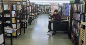 Student som läser en bok i arkivet books isolerat gammalt för begrepp utbildning lager videofilmer