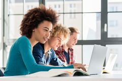 Student som ler, medan genom att använda en bärbar dator för online-information eller v fotografering för bildbyråer