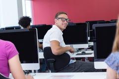 Student som ler på kameran i datorgrupp Arkivbild