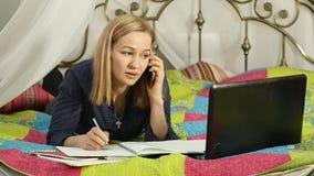Student som ligger på en säng i hem henne bärbar datorkvinnaworking on-line utbildning långsam rörelse stock video