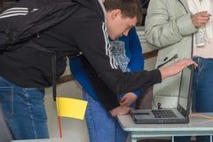 Student som lutar över att se en bärbar datorskärm royaltyfria foton