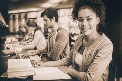 Student som ser kameran, medan studera med klasskompisar arkivbild