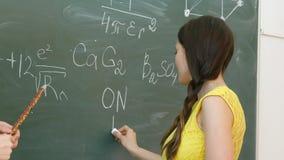 Student som skriver kemiskt symbol på svart tavla Royaltyfri Foto