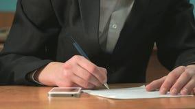 Student som skriver texten genom att använda pennan i dokument stock video