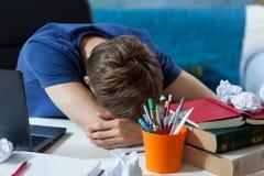 Student som sover på hans anmärkningar arkivbild