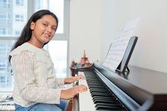 Student som spelar pianot royaltyfri bild