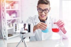 Student som studerar kemi genom att använda fotoställningen som gör bloggen om experiment royaltyfria foton