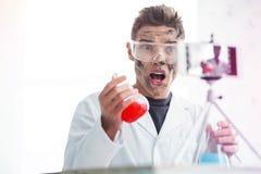Student som studerar kemi i laboratoriumet som har den smutsiga framsidan efter explosion arkivfoto
