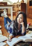 Student som studerar på golvläseböckerna arkivbilder