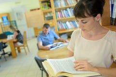 Student som studerar på tabellen royaltyfria bilder