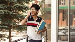 Student som talar vid mobiltelefonen arkivfilmer