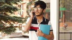 Student som talar vid smartphonen lager videofilmer