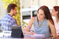 Student som tar anmärkningar som e-lär i en stång arkivfoton