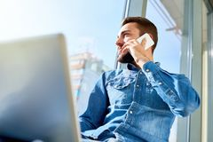 Student Speaking by Phone. Low angle portrait of handsome bearded man speaking by phone while working with laptop sitting on sunlit windowsill Royalty Free Stock Image