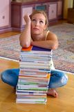 Student with a stack of books and computers. A student sits in front of a stack of books to learn the royalty free stock photos