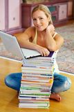 Student with a stack of books and computers. A student sits in front of a stack of books to learn the stock image