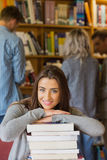 Student with stack of books while others in background at library Royalty Free Stock Photo