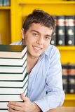 Student With Stacked Books Smiling At Table In Stock Photo