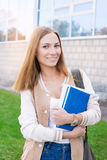 Student standing with books on building background. Student standing with books in her hands on building background royalty free stock photo